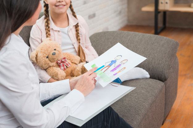 Woman sitting on a couch, holding a pencil and a child's drawing while talking to a young girl.